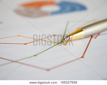 Close pen on business line charts and graph (Selective focus)