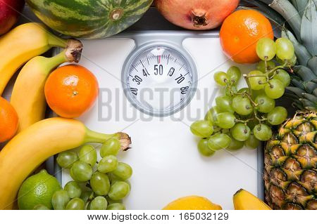 Stack of fruits over white weight scale. Concept of diet and healthy lifestyle
