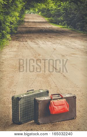 Two old suitcases and red bag standing on the road
