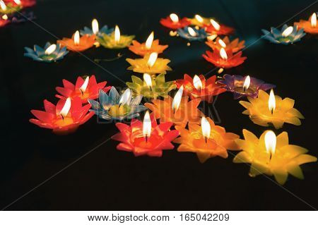 Close focus on colorful candles with fire floating on oil pool in low key tone. People float candles for lucky wishing.