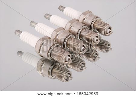 Four new spark plugs on a mirror background