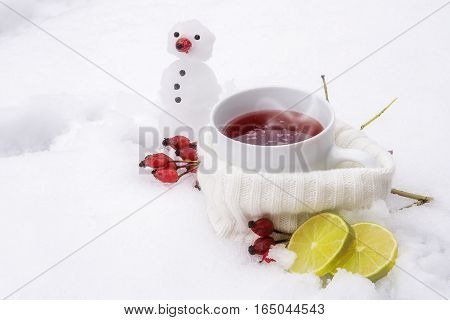 Hot tea with rose hips and lemons outside in the snow and a little snowman vitamin winter drink against flu and common cold selected focus