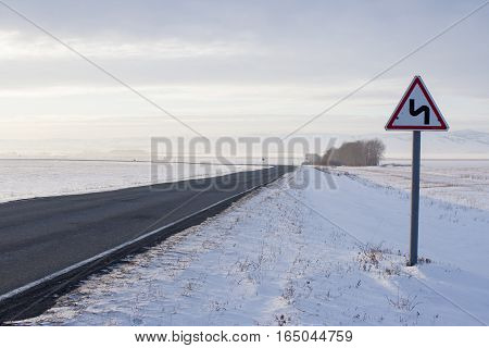 Winter road and traffic sign