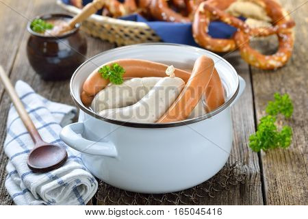 Hot Bavarian white sausages and wiener in an enamel cooking pot served on a wooden table with fresh pretzels and sweet mustard