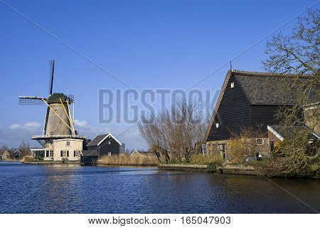 View over the Graafstroom river with the Dutch windmill De Vriendschap in the village Bleskensgraaf