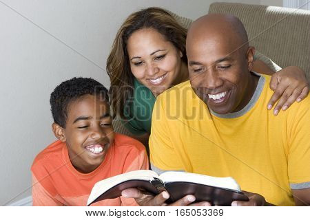 Happy African American family reading The Bible.