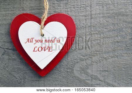 All You Need Is Love.Decorative red and white wooden hearts on a grey wooden background.Two Valentine hearts.Valentine's Day or Love concept.Selective focus.