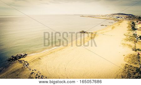 aerial view of a beach in southern france along the mediterranean coast with the city of sete in the background