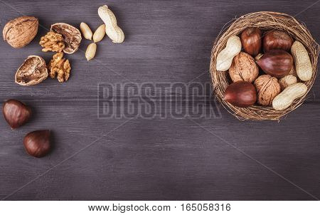 Mix nuts (chestnut peanut walnuts) in a bowl on a wooden background.