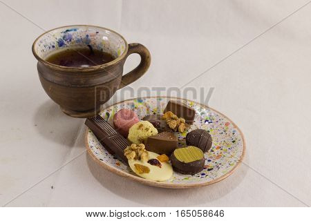 A variety of sweets on the saucer with a cup of tea on white background