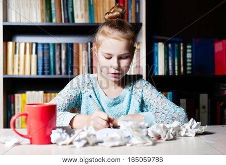 Schoolgirl Sitting At Table With Pencil In Hand.
