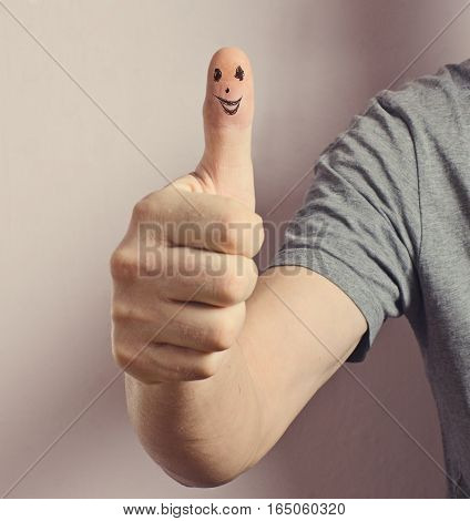 Hand with a raised thumb. Finger painted eyes and mouth