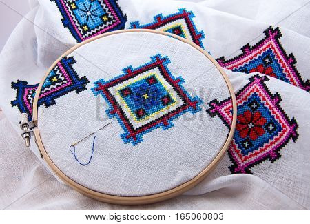 Traditional Slavic geometric pattern embroidered cross stitch multicolored thread white fabric in the wooden embroidery hoop