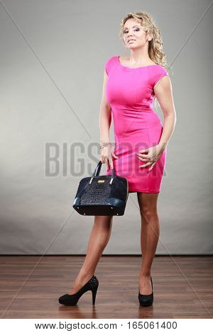 Beauty and fashion. Middle aged fashionable woman in full length wearing pink dress high heels shoes holds handbag studio shot on gray