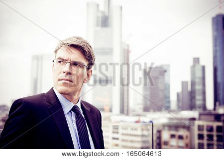 businessman with the skyline of frankfurt main in the background