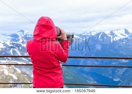 Tourism vacation and travel. Woman looking through sightseeing binoculars tourist telescope overlooking Geirangerfjord and mountains landscape from Dalsnibba viewpoint Norway