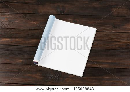 Mock-up magazine or catalog on wooden table. Blank page or notepad on wood background. Blank page or notepad for mockups or simulations.