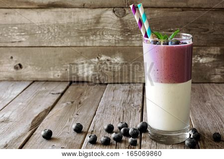 Layered Blueberry And Coconut Smoothie With Berries And Mint Against A Rustic Wooden Background