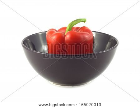 One ripe red bell pepper in purple bowl isolated over white closeup
