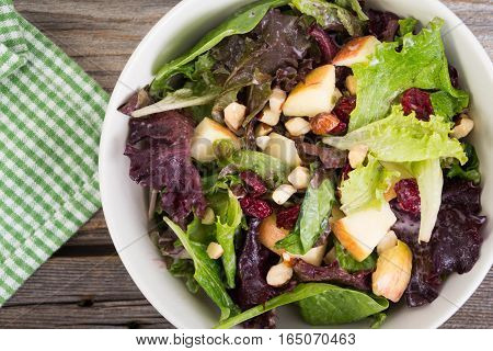 apple cranberry and nuts salad mix over rustic wood plank background