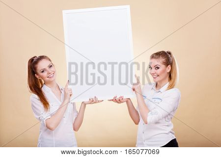Advertisement concept. Teenage smiling girls holding blank presentation board. Young women showing banner sign billboard copy space for text