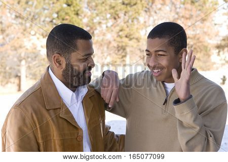 Happy African American father and his teenage son.