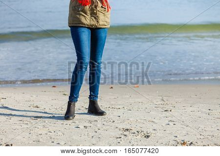 Leisure spending free time outside healthy walks concept. Woman wearing warm jacket relaxing on beach near sea cold sunny day