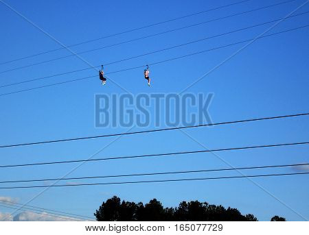 two people zip lining blue sky focus