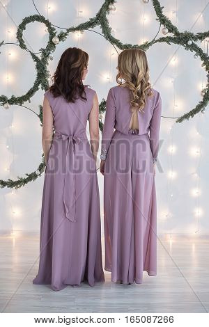 Two Young beautiful woman with hair of average length in an evening dress in front of a white wall decorated with fairy lights and fir branches poses for the camera.
