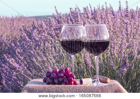 A photo of two glasses of red wine with grapes in a lavender field. The glasses are on a crate with a burlap texture, retro corkscrew and a cork. Toned image