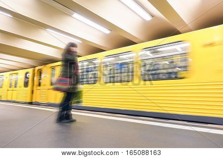 Defocused person standing in front speeding train - Underground transportation concept with blurred vehicle moving in subway - Generic metro public transport and unrecognizable woman with autumn wear