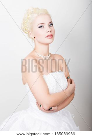 Beautiful blond bride wearing white dress with professional make-up.