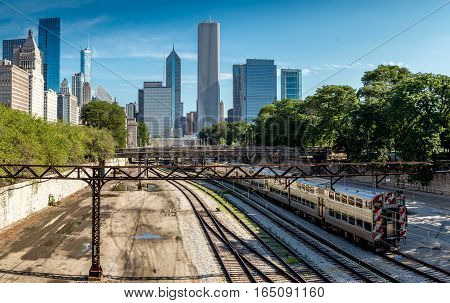 Train and rail lines with Chicago skyline at the background on a sunny day