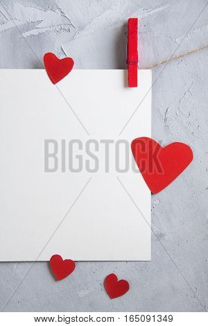 Valentine love background with white sheet of paper and red paper hearts hanging onto clothespins on a rope. Vertical orientation gray concrete background place for text.