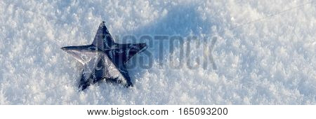 Blue star in the snow. Winter snow background