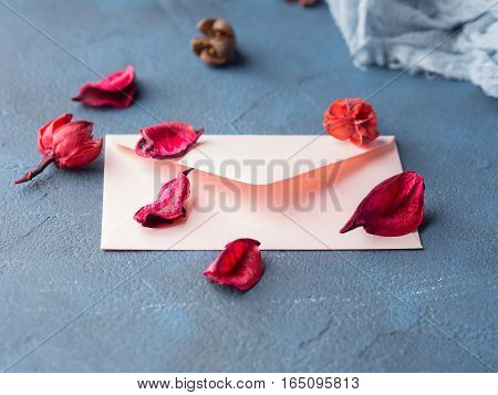 Pink envelope with dried flowers petals on dark blue background. Valentine's day. Sending Love letter