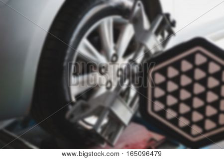 Car on stand with sensors on wheels for wheels alignment camber check in workshop of Service station (blur image)