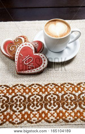 Cup of a perfection. High angle shot of a cup of coffee with froth design and three glazed red Valentine s day cookies on the table