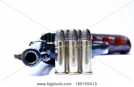 Revolver with bullets on the table against the background.