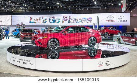 DETROIT MI/USA - JANUARY 12 2017: A custodian polishes a car near a 2018 Toyota Camry at the North American International Auto Show (NAIAS).