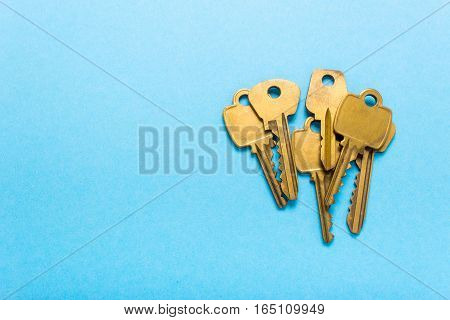 A bunch of golden keys lies on a blue background