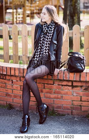 Happy beautiful woman with long legs sitting in the park