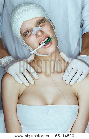 Furious beauty victim with syringe in her mouth. Doctor with patient in medical bandage. Lip augmentation. Beauty injections