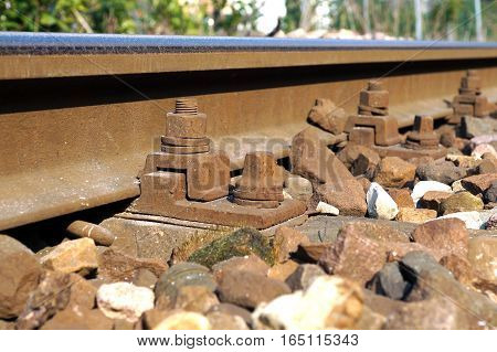 The crushed stones or ballast alongside the rail track hold the wooden cross ties in place, which in turn lock the rail in place due to their sharp edges.