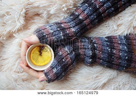 Her hands in mittens holding a cup of tea with lemon on a white background.