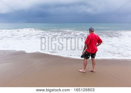 Man walking exploring beach ocean coastline with rain clouds on horizon