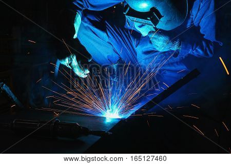 Welder of Metal Welding with sparks and smoke in manufacturing