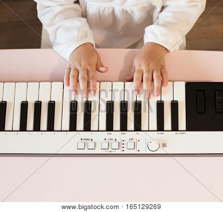 Little girl's hands playing electronic piano. Process of education, cognition