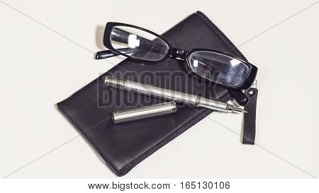Leather cover, the glasses and the metal pen on the white background