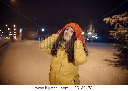 the girl's portrait on a city footpath, in the winter during snowfall, against the background of church, a magnificent fir-tree and a number of lamps. the evening lit with blue fires